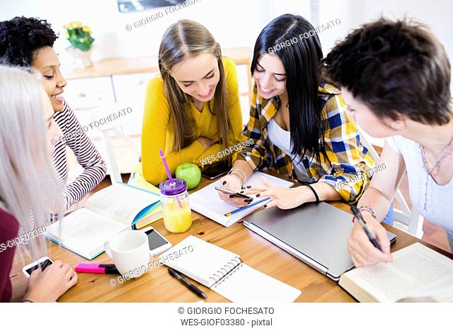 Group of female students sharing cell phone at table at home