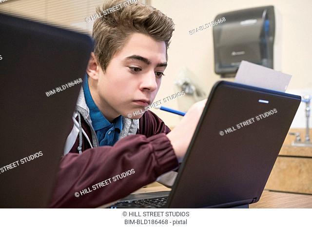 Caucasian student using laptop in classroom