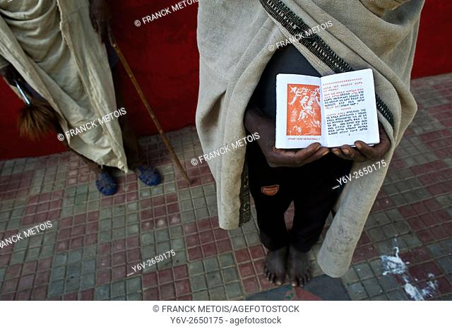 A religious student is showing his study book. On the left side, an orthodox priest is visible. The scene takes place in an orthodox christian church near Korem...
