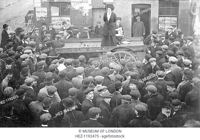 Isabel Seymour addressing a crowd of men and boys from a tradesman's cart, 1908. Seymour worked in the office and Clement's Inn
