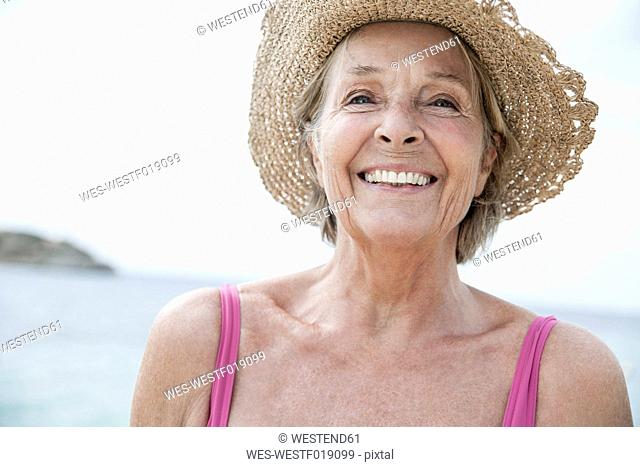 Spain, Senior woman with straw hat on beach