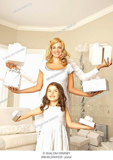 Hispanic family holding Christmas gifts in outstretched arms