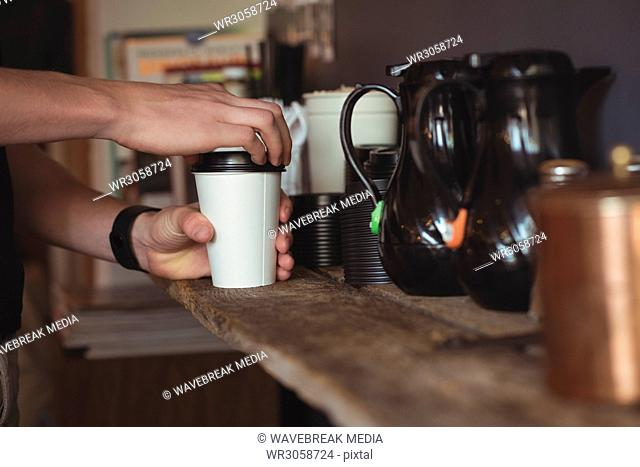 Mid section of waiter preparing coffee