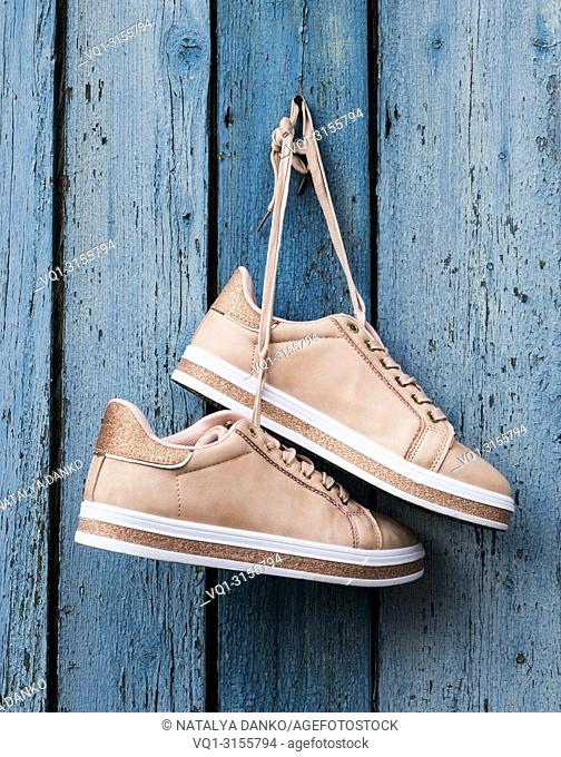 pair of beige fashionable female sports shoes hanging on a cord on a background of a blue old wooden wall