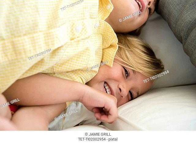 Boy (4-5) and girl (6-7) playing on sofa