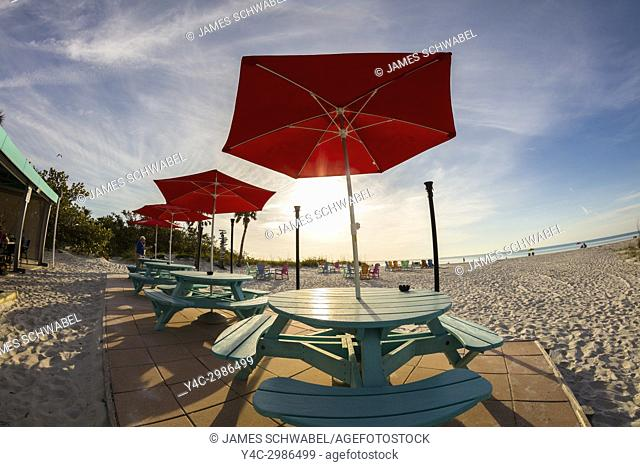 Picnic tables and chairs on the beach on a sunny day at the South Beach Bar & Grill on Gasparilla Island Florida