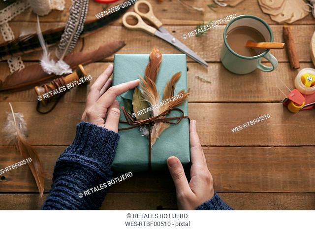 Woman decorating Christmas present with leaf and feathers, close-up