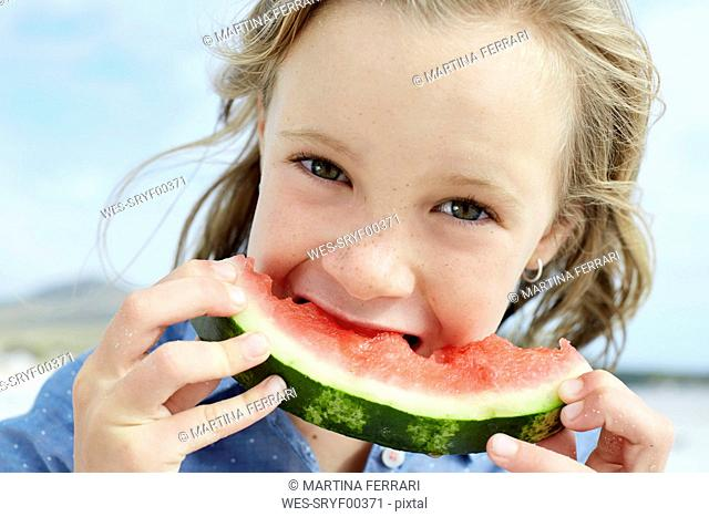 Little girl eating water melon in the beach
