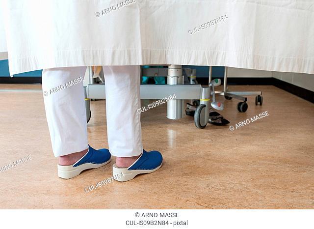 Feet of nurse behind hospital room privacy curtain