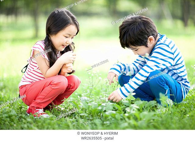 Side view of smiling boy and girl sitting and touching plants in field