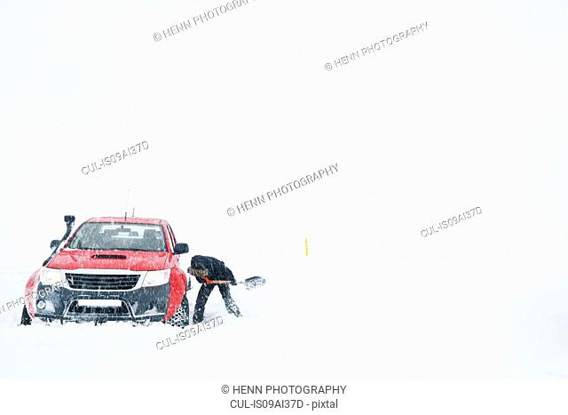 Mature woman digging out snow from stranded pick up truck, Fljotsheidi, North Iceland