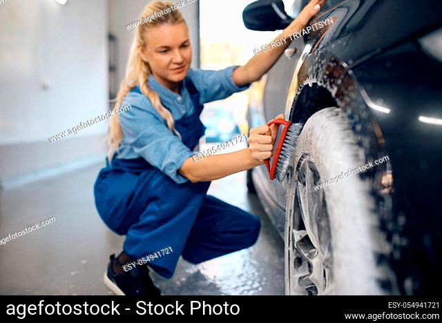 Female washer with brush in hand cleans wheel in foam, car wash. Woman washes vehicle, carwash station, car-wash business