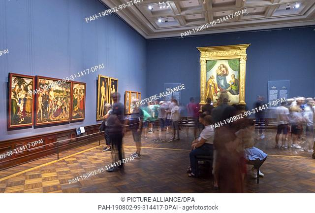 """02 August 2019, Saxony, Dresden: Numerous visitors are looking at Raffael's work """"""""Sistine Madonna"""""""" (r) in the exhibition """"""""Highlights of the Old Masters..."""