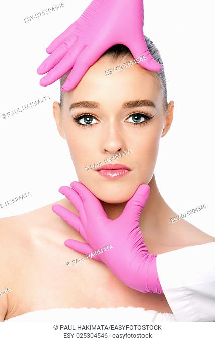 Beautiful face ready for Cosmetic skincare spa beauty treatment with pink gloves, on white