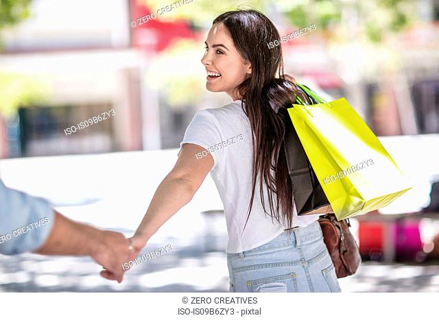 Young couple outdoors, holding hands, holding shopping bags, rear view