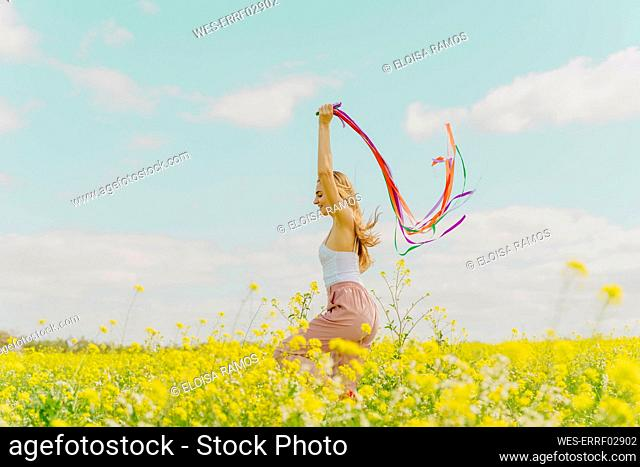Happy young woman moving with colourful ribbons in a flower meadow in spring