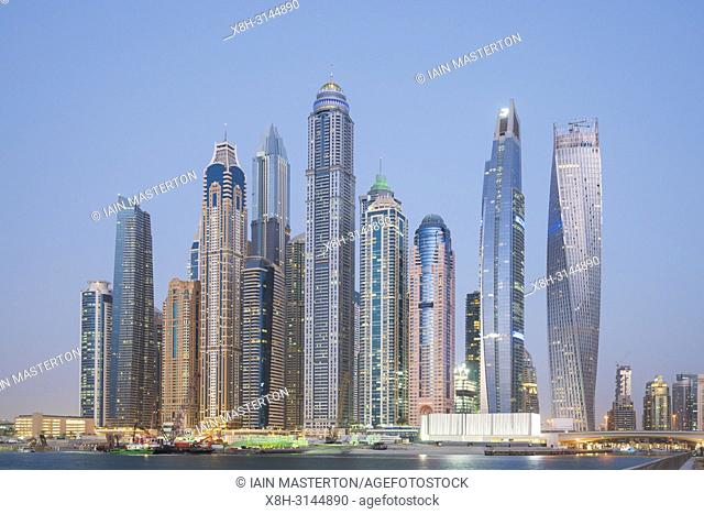 Many high rise apartment towers and skyscrapers at dusk in Marina district of Dubai, UAE, United Arab Emirates