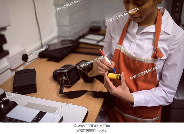 Female photographer marking a photo reel