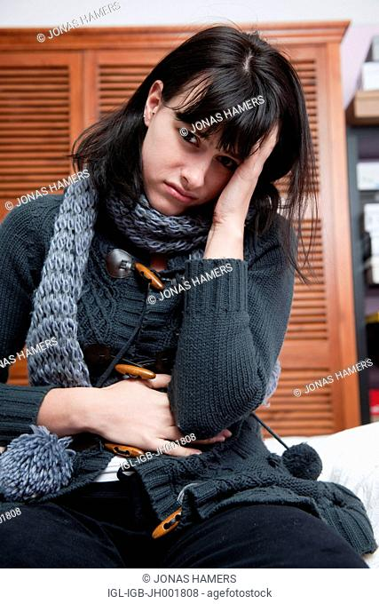 This picture shows a young caucasian woman with brown hair as she sits on her bed feeling ill / sick or tired