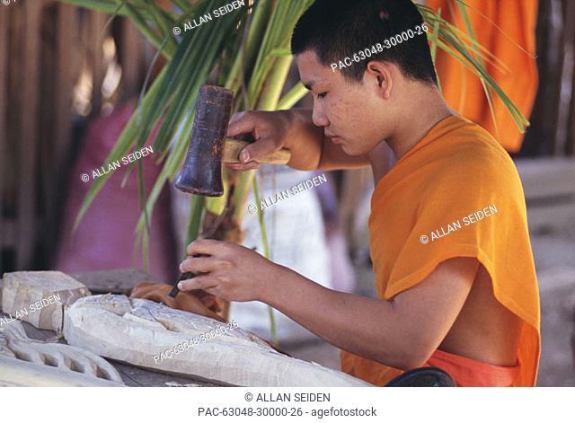 Laos, Luang Prabang, Young monk carving a wood filigree