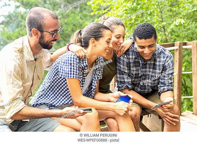 Italy, Massa, smiling hikers in the Alpi Apuane mountains looking at their smartphones and sitting on a bench
