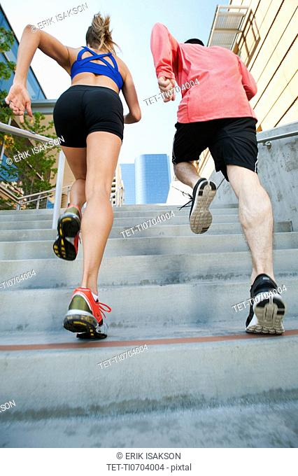 USA, California, Los Angeles, Young man and young woman running on city street