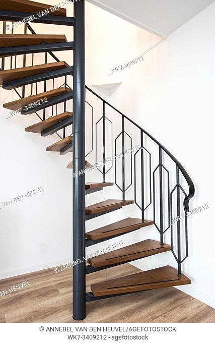 Close up of a iron exterior spiral staircase on the side of a modern house with white wall clean