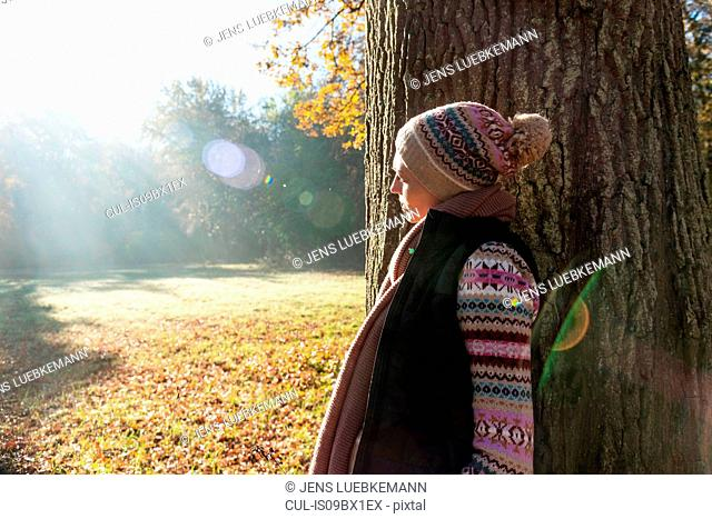 Woman leaning against tree in park, Strandbad, Mannheim, Germany