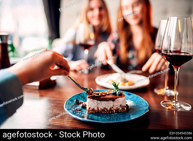 Young women eats sweet cakes in restaurant. Chocolate dessert and alcohol on the table