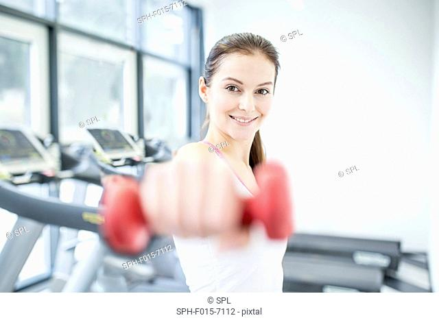 MODEL RELEASED. Smiling young woman working out with dumbbell in gym, portrait