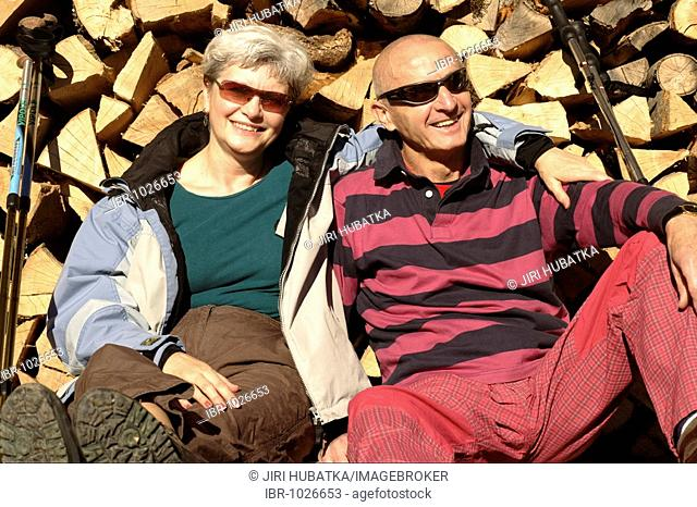 Old-aged couple relaxing in front of a stack of wood