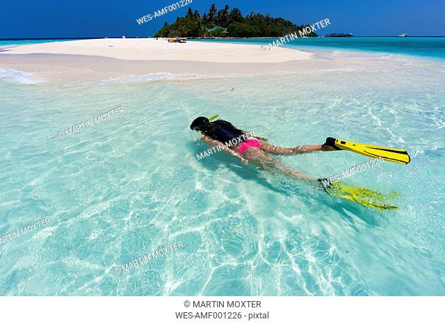 Maledives, young woman snorkelling in a lagoon