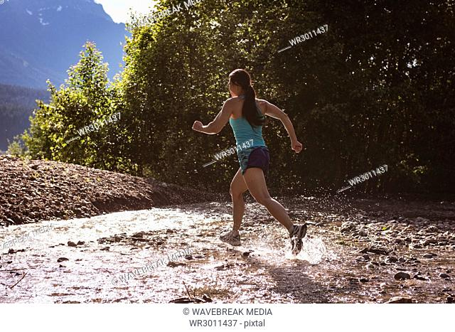 Fit woman jogging in water