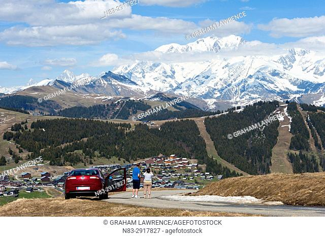 A couple park their car on Mont Bisanne and look towards the ski resort of Les Saisies and the Mont Blanc Massif in the distance, Les Saisies, Savoie, France