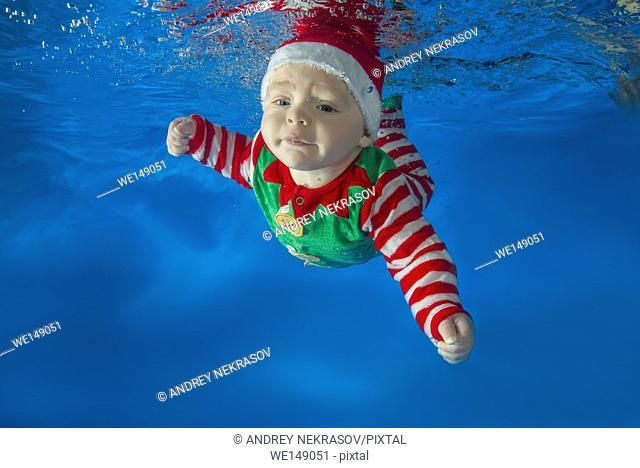 A little boy dressed as Santa's helper floats under water in the pool