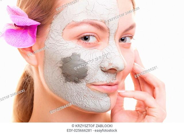 skin care. young woman applying clay mask on her face. girl taking care of her dry compexion. isolated. spa and beauty treatment