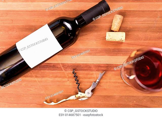 Wine in details. Top view of bottle and wineglass with red wine on the wooden table