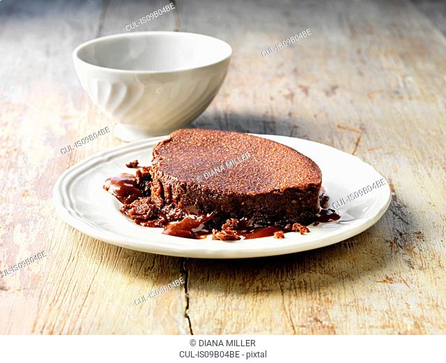 Hot chocolate fudge pudding on white plate, white bowl, wooden table