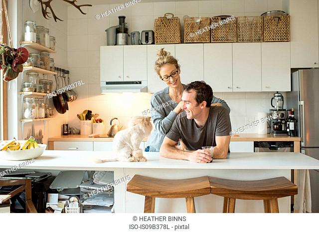 Mid adult couple with cat at kitchen counter