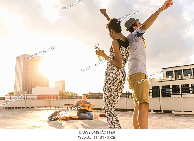 Young couple dancing on a rooftop party