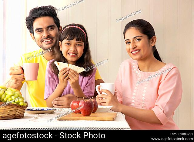 A CHEERFUL FAMILY LOOKING AT CAMERA WHILE EATING BREAKFAST