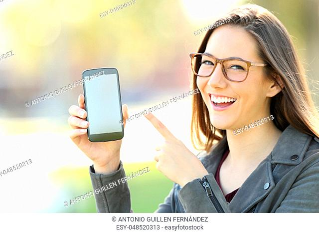 Happy woman wearing eyeglasses showing a blank phone screen in the street
