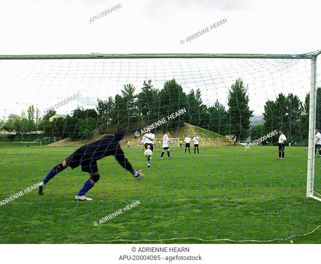 Goalkeepr dives to his right to save a shot from field player during warm-up