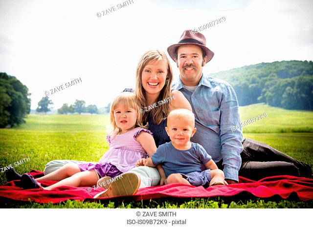 Portrait of mid adult couple sitting on picnic blanket with daughter and baby son