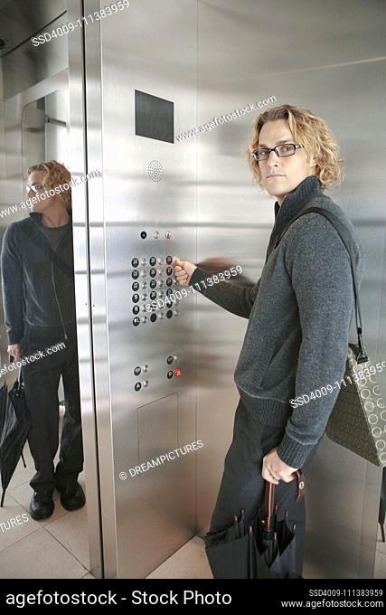 Caucasian man pressing elevator buttons