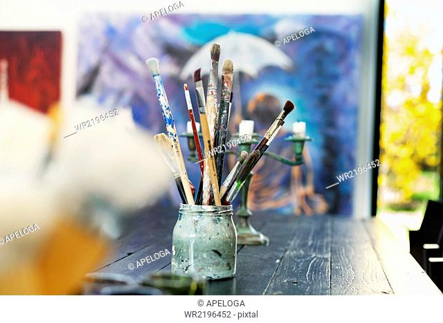 Paintbrushes in container on table at art studio