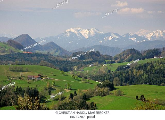 Farmhouses and snow covered mountains of the alps Mostviertel view from the scenic road Alpenvorlandstraße Lower Austria