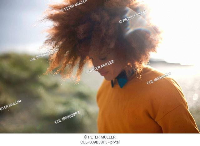 Woman with afro hair on grassy dune