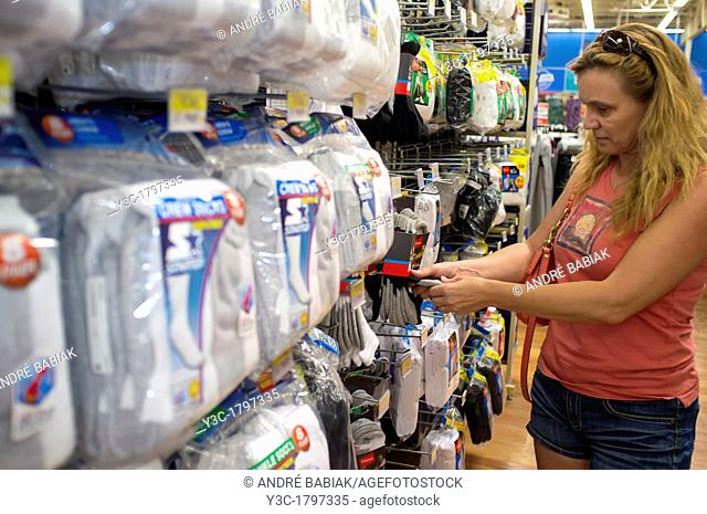 Woman picking clothes from a socks shelf at a store aisle