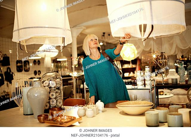 Woman looking at lamp in shop